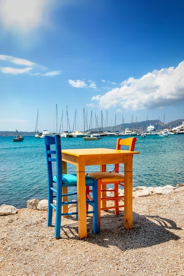 Ένα πολύχρωμο τραπέζι και καρέκλες δίπλα στη γαλάζια θάλασσα, Μίλος, Ελλάδα στοκ φωτογραφία με δικαίωμα ελεύθερης χρήσης