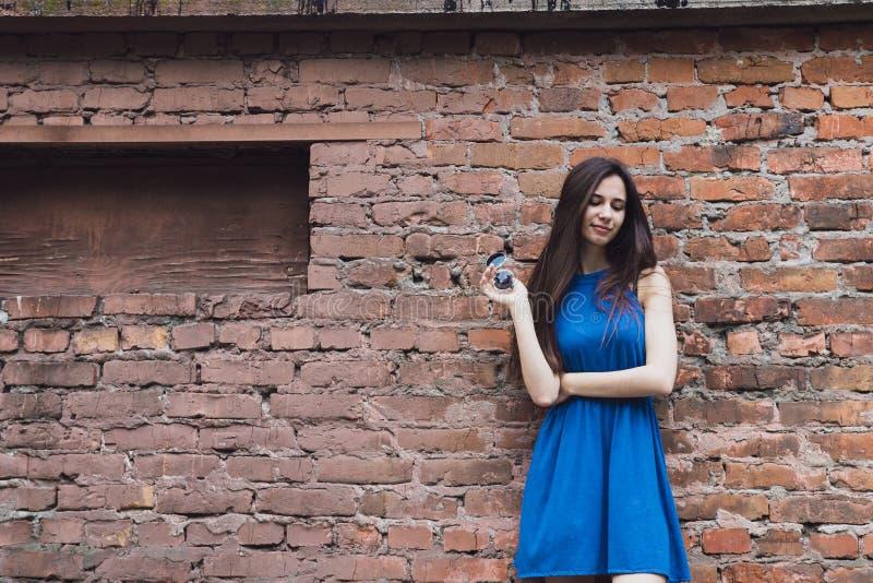 Ένα πολύ όμορφο και εύθυμο κορίτσι στέκεται στην οδό κοντά σε έναν τουβλότοιχο στοκ φωτογραφία