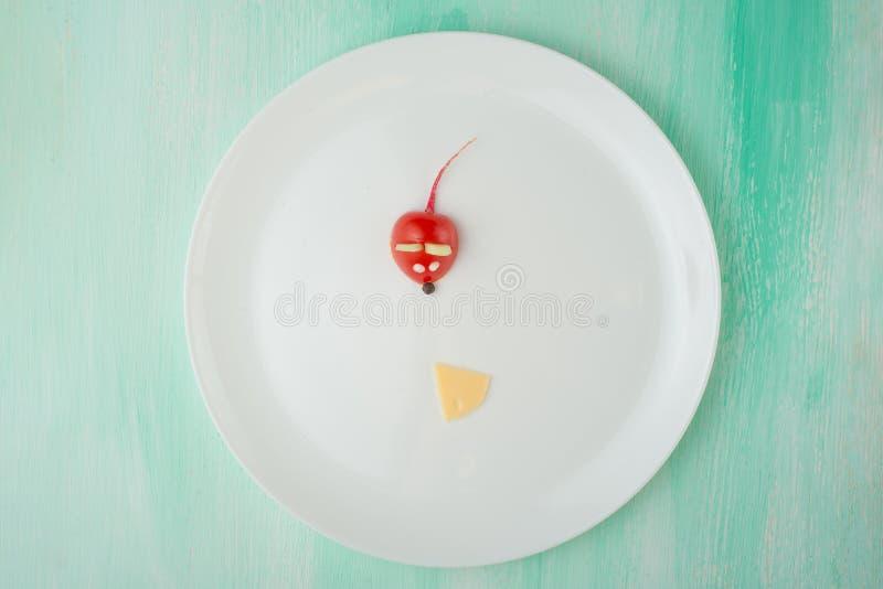 Ένα ποντίκι από μια ντομάτα και μια φέτα του τυριού, ένας δημιουργικός από τα τρόφιμα σε ένα άσπρο πιάτο Η έννοια της κατανάλωσης στοκ εικόνα