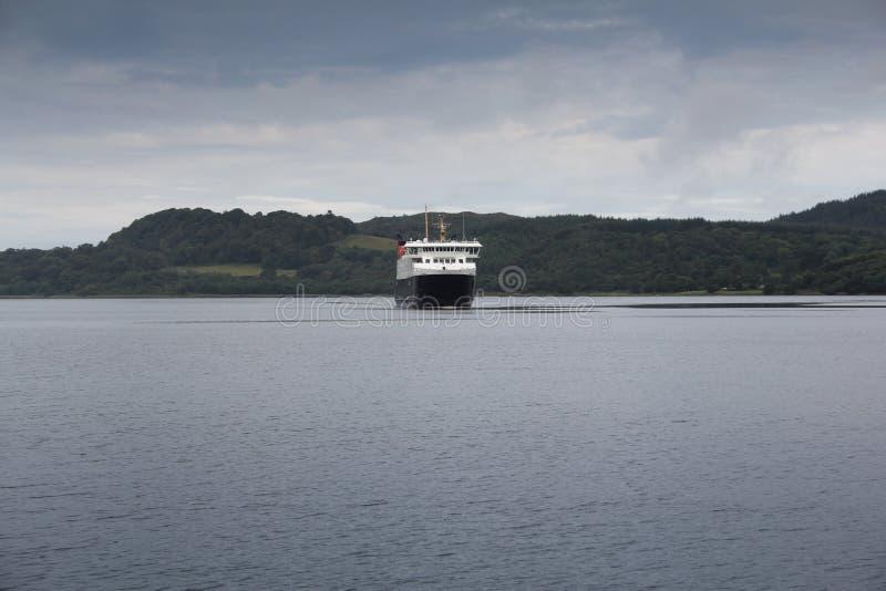 Ένα πορθμείο που πλησιάζει έναν λιμένα στην ακτή της Σκωτίας μια κρύα θερινή ημέρα στοκ εικόνες