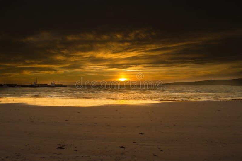 Ένα πορτοκαλί ηλιοβασίλεμα σε μια παραλία στα Orkney νησιά στοκ εικόνα