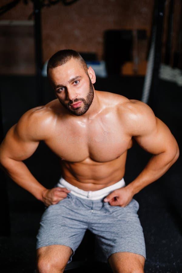 Ένα πορτρέτο ενός αρσενικού με τους μυς κάμψης σε ένα υπόβαθρο γυμναστικής Ένα bodybuilder με ένα τέλειο σώμα ασκώντας την ικανότ στοκ φωτογραφία