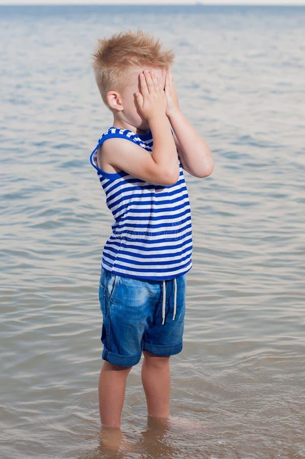 Ένα πορτρέτο ενός μικρού αγοριού το του οποίου πρόσωπο είναι κρυμμένο με τα χέρια του Χ στοκ φωτογραφία