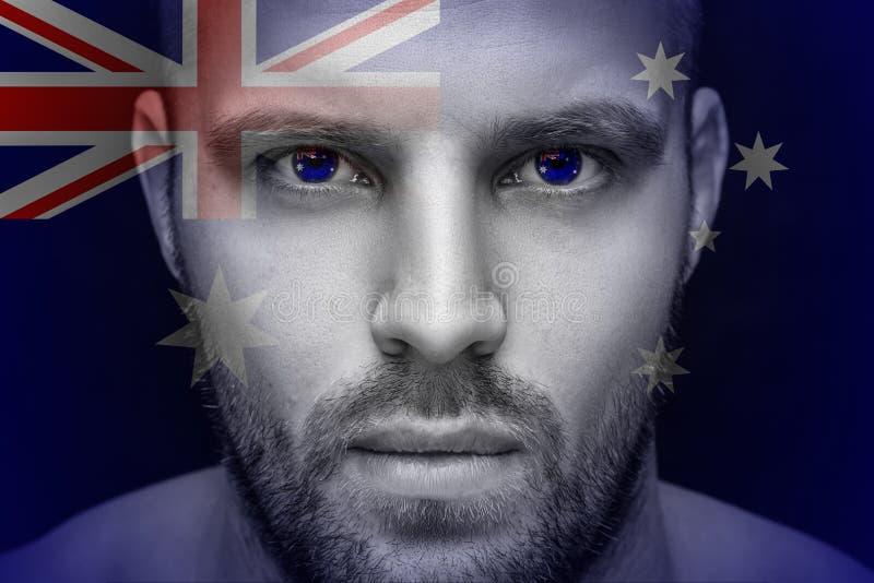 Ένα πορτρέτο ενός νέου σοβαρού ατόμου, στα του οποίου μάτια απεικονίζεται τη εθνική σημαία στοκ φωτογραφία με δικαίωμα ελεύθερης χρήσης