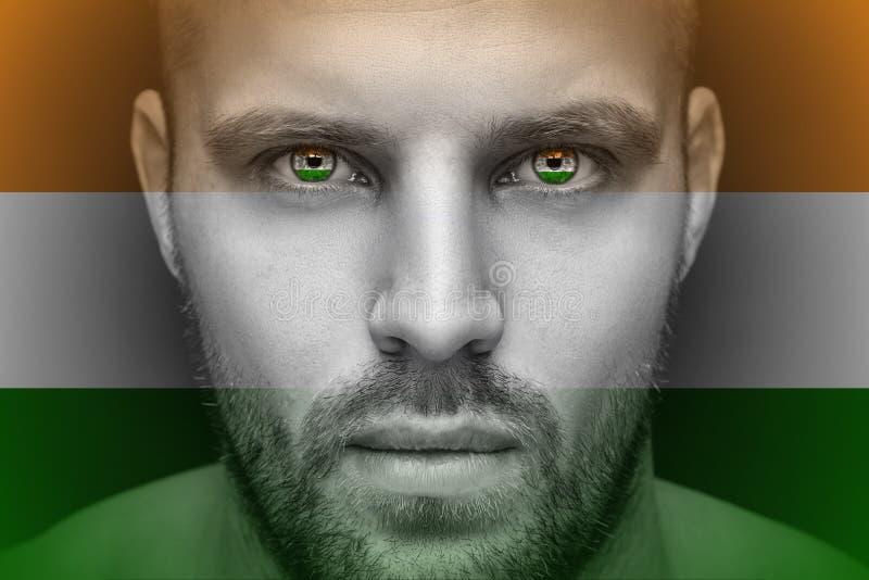 Ένα πορτρέτο ενός νέου σοβαρού ατόμου, στα του οποίου μάτια απεικονίζεται τη εθνική σημαία στοκ εικόνα