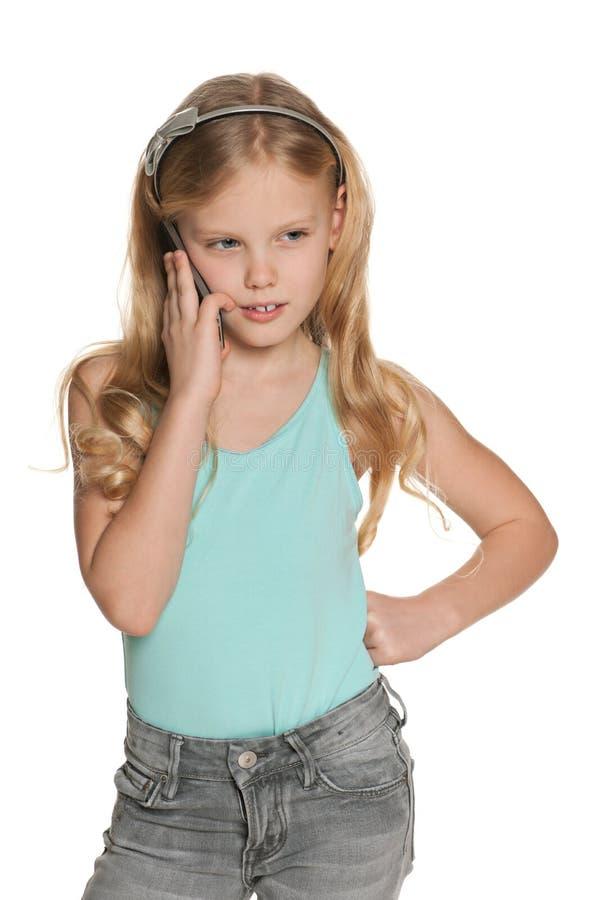 Ξανθό κορίτσι με ένα τηλέφωνο κυττάρων στοκ εικόνα