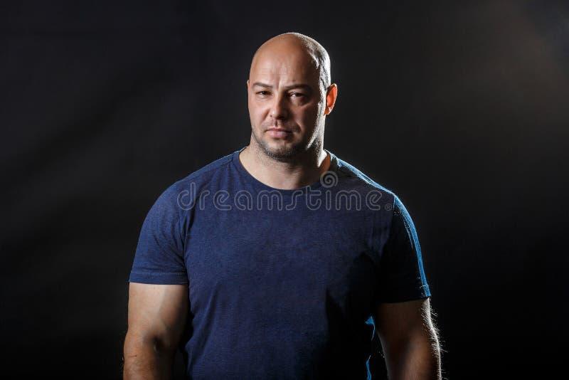 Ένα πορτρέτο ενός φουσκωμένου άτριχου άντρα με σκούρο μπλουζάκι στοκ εικόνες