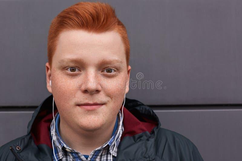 Ένα πορτρέτο κινηματογραφήσεων σε πρώτο πλάνο του ελκυστικού redhead φακιδοπρόσωπου αγοριού με το στρογγυλό πρόσωπο που έχει το μ στοκ εικόνες
