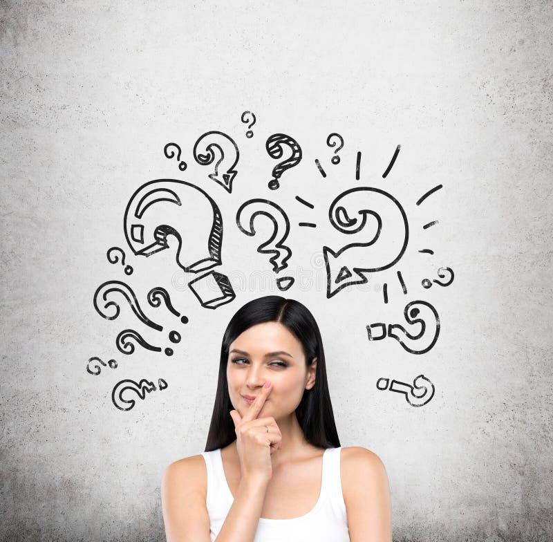 Ένα πορτρέτο μιας νέας έξυπνης κυρίας brunette που προσπαθεί να ανακαλύψει μια λύση κάποιου προβλήματος Η κυρία είναι σε μια άσπρ στοκ φωτογραφίες