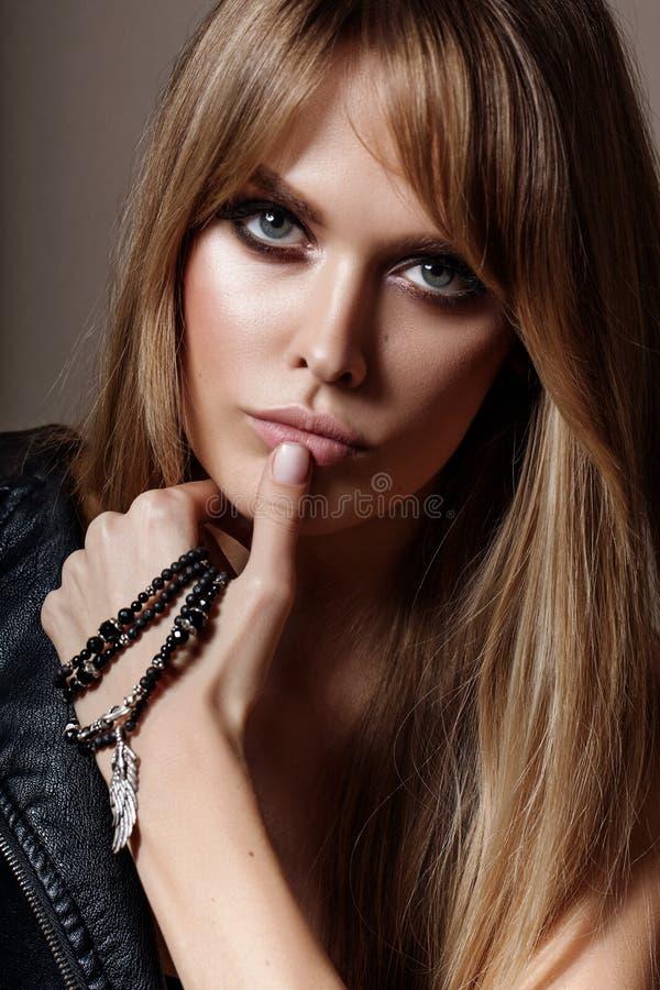 Ένα πορτρέτο μιας νέας γοητευτικής γυναίκας που φορά το μοντέρνο περιδέραιο και τα διαπερασμένα σκουλαρίκια στοκ εικόνες