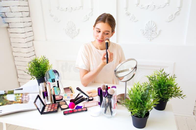 Ένα πορτρέτο της γυναίκας με τις βούρτσες makeup κοντά στο πρόσωπο στοκ φωτογραφία