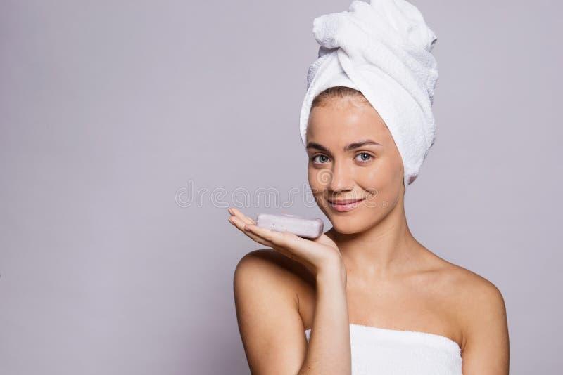 Ένα πορτρέτο της νέας γυναίκας με έναν φραγμό του σαπουνιού σε ένα στούντιο, μια ομορφιά και μια φροντίδα δέρματος στοκ φωτογραφίες