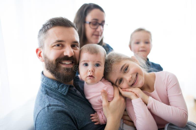 Ένα πορτρέτο της νέας οικογένειας με τα μικρά παιδιά που κάθονται στο εσωτερικό σε έναν καναπέ στοκ εικόνες
