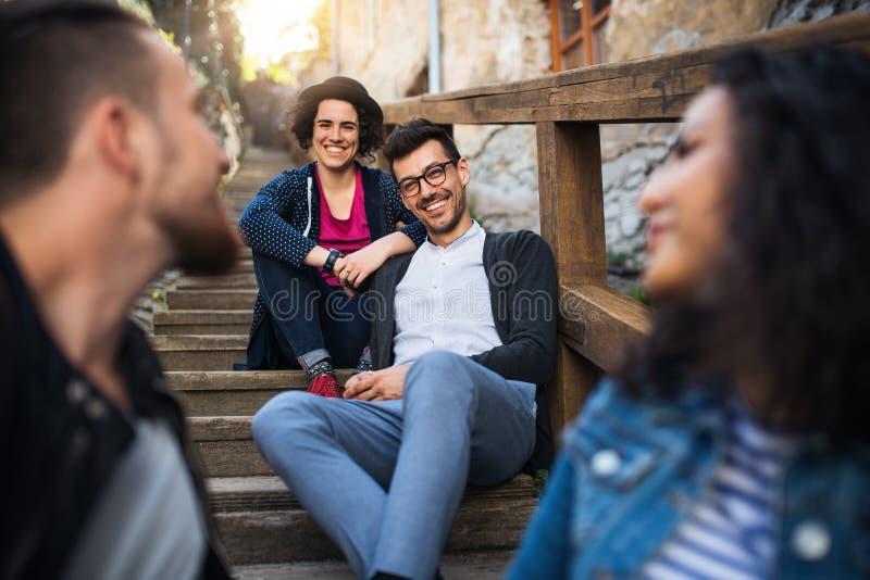 Ένα πορτρέτο της ομάδας νέων φίλων που κάθονται υπαίθρια στη σκάλα στην πόλη στοκ εικόνες