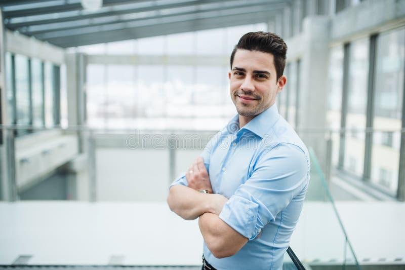 Ένα πορτρέτο του νέου επιχειρηματία που στέκεται στο εσωτερικό σε ένα γραφείο, όπλα που διασχίζονται στοκ εικόνες