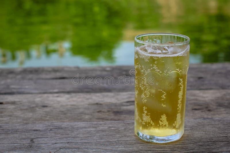 Ένα ποτήρι της μπύρας με τον πάγο στον ξύλινο πίνακα, που πίνει στην καυτή ασιατική χώρα με το δροσερό μη αλκοολούχο ποτό στοκ φωτογραφίες