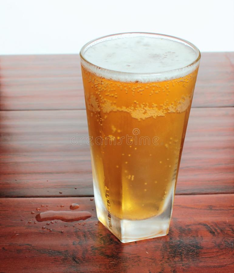 Ένα ποτήρι της μπύρας ξανθού γερμανικού ζύού στέκεται στο μπουκάλι επιτραπέζιων κτύπημα-κορυφών στοκ εικόνες