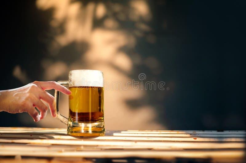 Ένα ποτήρι της μπύρας στον πίνακα στη θερινή ηλιόλουστη ημέρα Η κατανάλωση ανθρώπων παρασκευάζει στοκ εικόνες