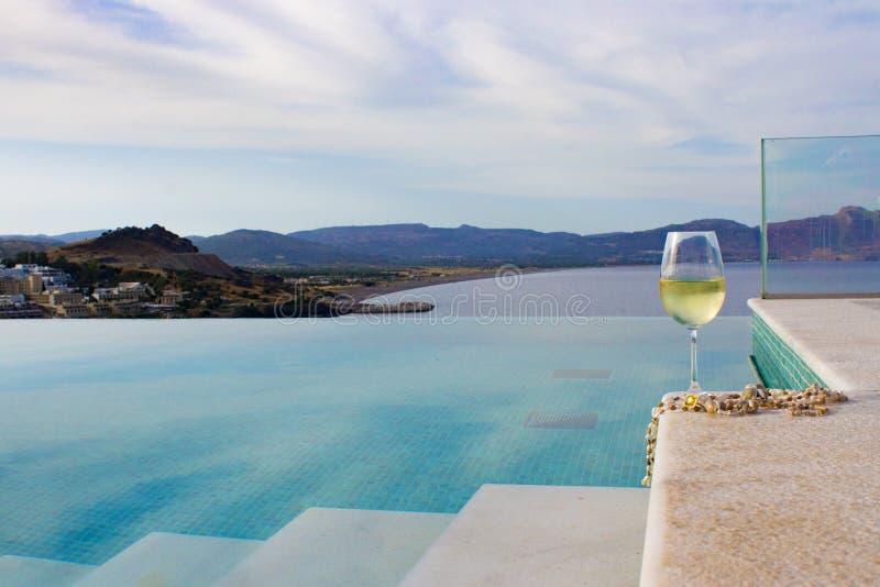ένα ποτήρι του άσπρου κρασιού με τις χάντρες κοχυλιών βρίσκεται στην άκρη των σκαλοπατιών λιμνών στοκ φωτογραφία