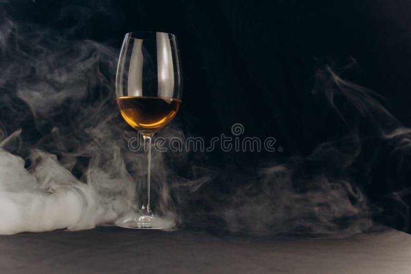 Ένα ποτήρι του άσπρου κρασιού σε ένα μαύρο υπόβαθρο ο καπνός από το hookah τυλίγει το γυαλί υπόλοιπο, διακοπές οινοπνευματώδης κι στοκ εικόνα με δικαίωμα ελεύθερης χρήσης
