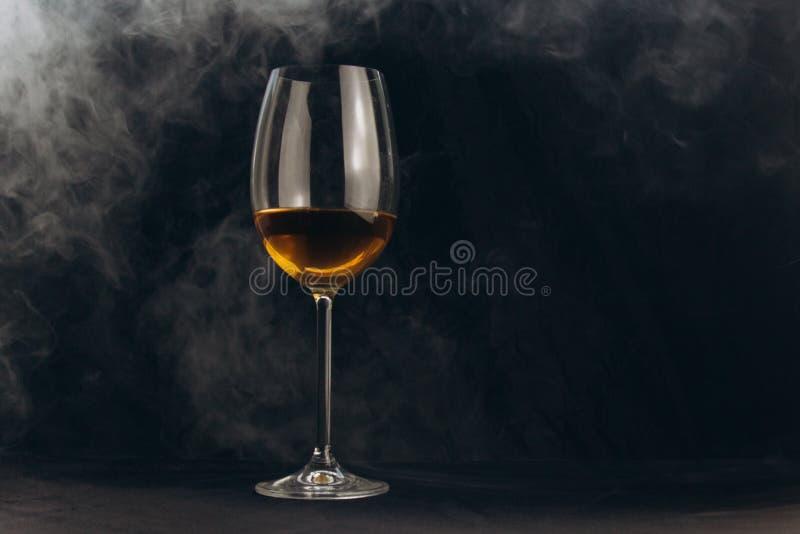 Ένα ποτήρι του άσπρου κρασιού σε ένα μαύρο υπόβαθρο ο καπνός από το hookah τυλίγει το γυαλί υπόλοιπο, διακοπές οινοπνευματώδης κι στοκ εικόνες