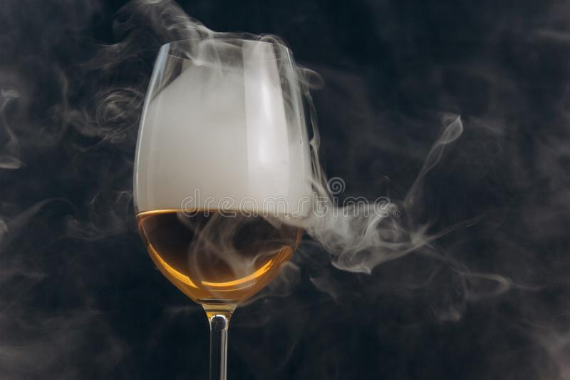 Ένα ποτήρι του άσπρου κρασιού σε ένα μαύρο υπόβαθρο ο καπνός από το hookah τυλίγει το γυαλί υπόλοιπο, διακοπές οινοπνευματώδης κι στοκ φωτογραφία με δικαίωμα ελεύθερης χρήσης
