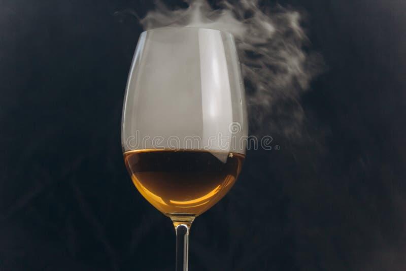 Ένα ποτήρι του άσπρου κρασιού σε ένα μαύρο υπόβαθρο ο καπνός από το hookah τυλίγει το γυαλί υπόλοιπο, διακοπές οινοπνευματώδης κι στοκ εικόνες με δικαίωμα ελεύθερης χρήσης