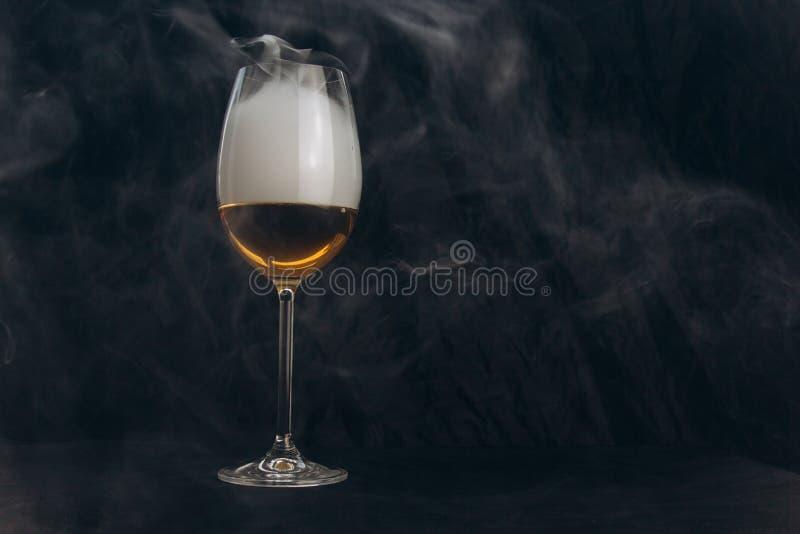 Ένα ποτήρι του άσπρου κρασιού σε ένα μαύρο υπόβαθρο ο καπνός από το hookah τυλίγει το γυαλί υπόλοιπο, διακοπές οινοπνευματώδης κι στοκ φωτογραφίες με δικαίωμα ελεύθερης χρήσης