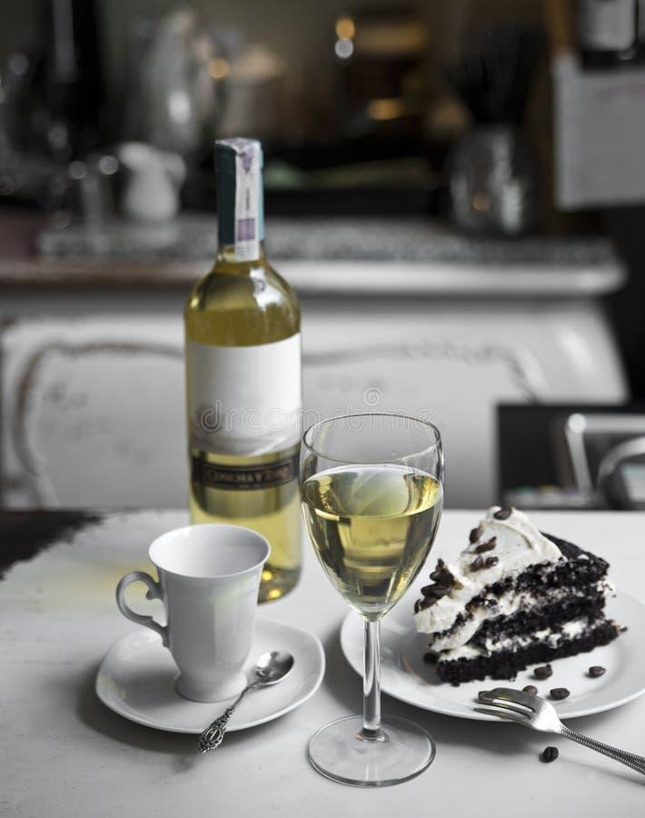 Ένα ποτήρι του άσπρου κρασιού, του φλυτζανιού, του κέικ σοκολάτας και ενός μπουκαλιού του κρασιού σε ένα αναδρομικό υπόβαθρο στοκ φωτογραφίες