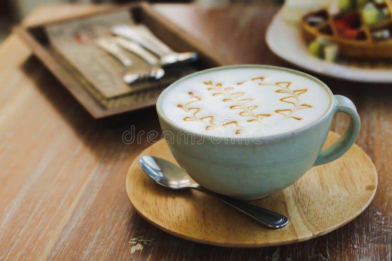 Ένα ποτήρι του καφέ με τον αφρό γάλακτος που ολοκληρώνεται με την καραμέλα σε έναν ξύλινο πίνακα στοκ εικόνες