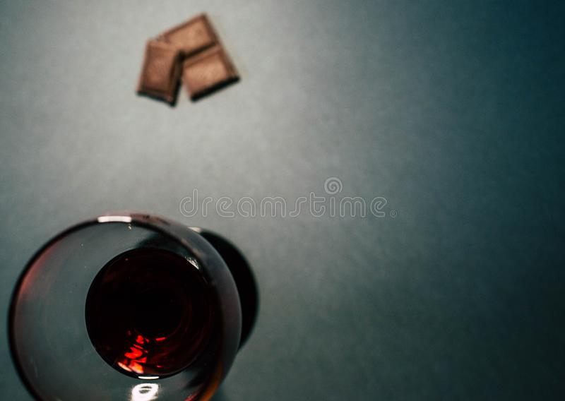 Ένα ποτήρι του κόκκινου κρασιού με τις φέτες σοκολάτας στοκ φωτογραφίες