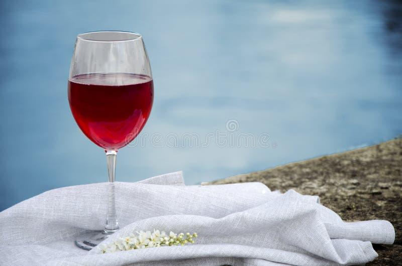 Ένα ποτήρι του κόκκινου κρασιού στέκεται σε μια υφαντική πετσέτα στις όχθεις του ποταμού στον ήλιο στοκ εικόνα