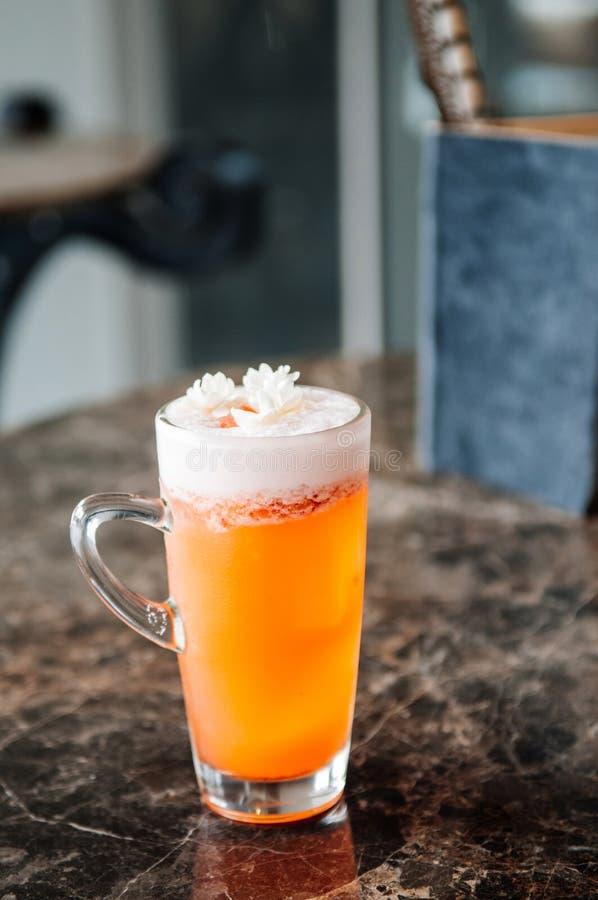 Ένα ποτήρι του πορτοκαλιού κοκτέιλ μπύρας τσαγιού της Jasmine με το χνουδωτό άσπρο αφρό και την ταϊλανδική Jasmine ανθίζει στοκ φωτογραφία με δικαίωμα ελεύθερης χρήσης