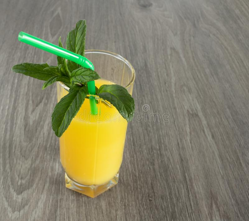 Ένα ποτήρι του χυμού από πορτοκάλι με ένα άχυρο που διακοσμείται με τα φύλλα μεντών στοκ εικόνες