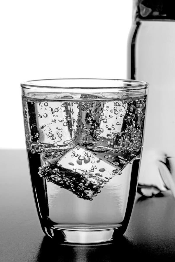 Ένα ποτήρι του ύδατος με τους κύβους πάγου στοκ εικόνα