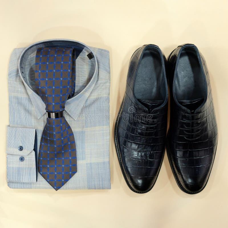 Ένα πουκάμισο με έναν δεσμό και τα παπούτσια βρίσκονται σε ένα μπεζ πάτωμα Εξαρτήματα μόδας του σύγχρονου ατόμου Τετραγωνικό πλαί στοκ φωτογραφία με δικαίωμα ελεύθερης χρήσης