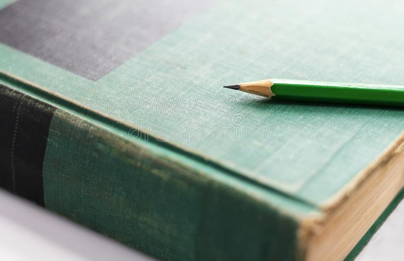 Ένα πράσινο ξύλινο μολύβι τοποθετείται στο βιβλίο με σκληρό εξώφυλλο ή το εγχειρίδιο Sel στοκ φωτογραφία με δικαίωμα ελεύθερης χρήσης
