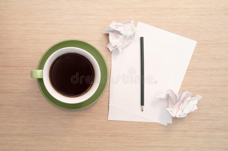 Ένα πράσινο φλιτζάνι του καφέ στον πίνακα και το κενό φύλλο, μολύβι, τσαλάκωσε τα απορρίματα στοκ εικόνα με δικαίωμα ελεύθερης χρήσης