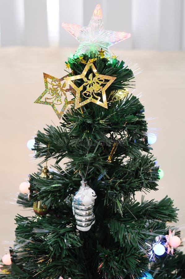 Ένα πράσινο χριστουγεννιάτικο δέντρο με έναν διαφανή άριστο αστεριών και άλλες διακοσμήσεις στοκ φωτογραφία με δικαίωμα ελεύθερης χρήσης