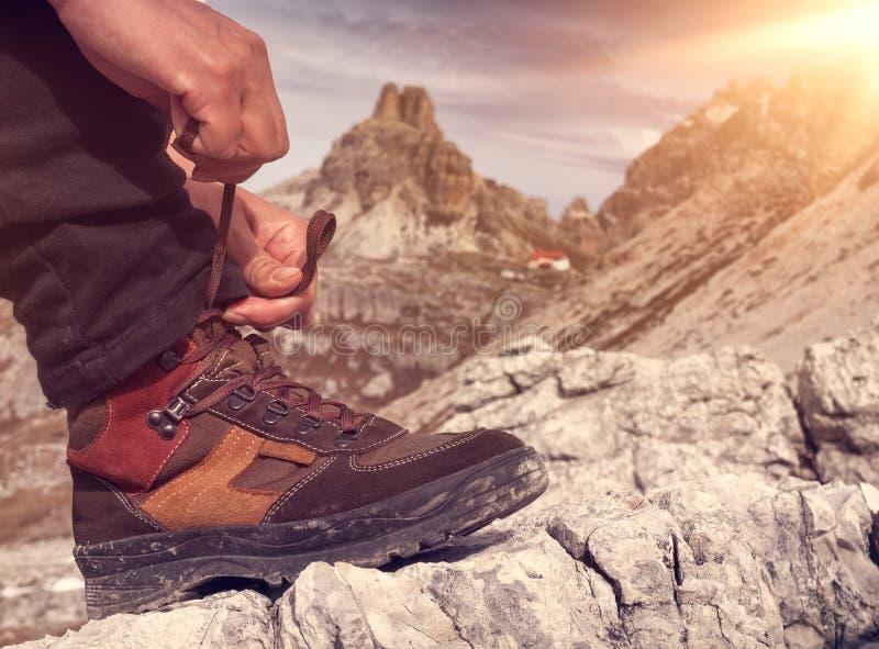 Ένα πρόσωπο δένει τα παπούτσια πεζοπορίας στην κινηματογράφηση σε πρώτο πλάνο βουνών στοκ εικόνες με δικαίωμα ελεύθερης χρήσης