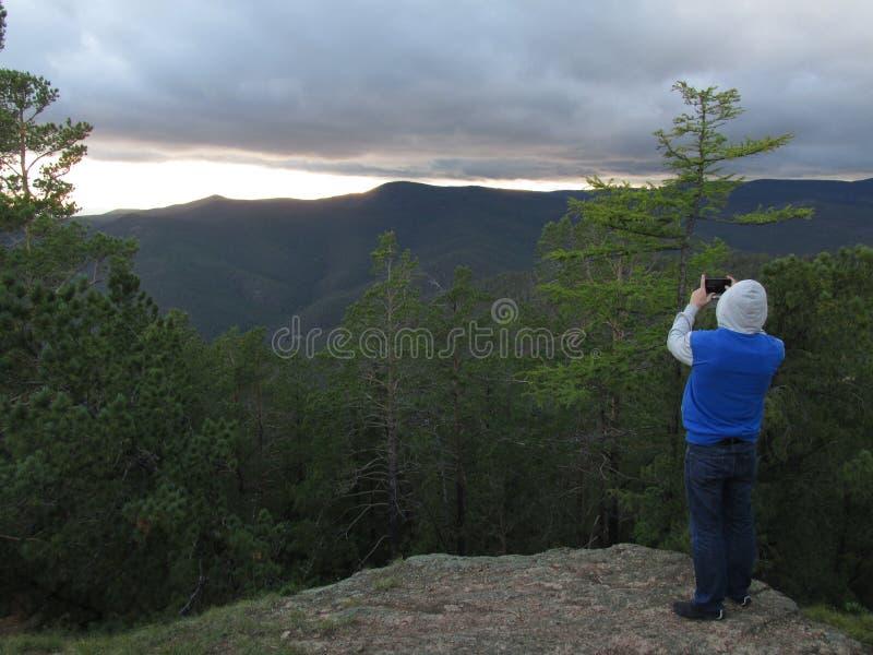 Ένα πρόσωπο παίρνει ένα ηλιοβασίλεμα στα βουνά Buryatia στοκ εικόνα