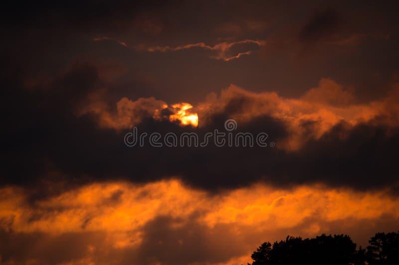 Ένα δραματικό ηλιοβασίλεμα πίσω από τα σύννεφα στοκ εικόνες