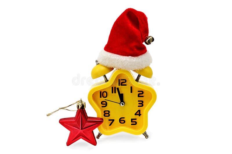 Ένα ρολόι Χριστουγέννων αστερίσκων παρουσιάζει υπόλοιπο χρόνο μέχρι τα μεσάνυχτα με ένα καπέλο Άγιου Βασίλη και έναν κόκκινο αστε στοκ φωτογραφία με δικαίωμα ελεύθερης χρήσης