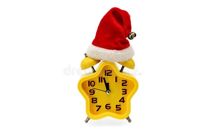 Ένα ρολόι Χριστουγέννων αστερίσκων παρουσιάζει υπόλοιπο χρόνο μέχρι τα μεσάνυχτα με ένα καπέλο Άγιου Βασίλη, σε ένα άσπρο υπόβαθρ στοκ εικόνες με δικαίωμα ελεύθερης χρήσης