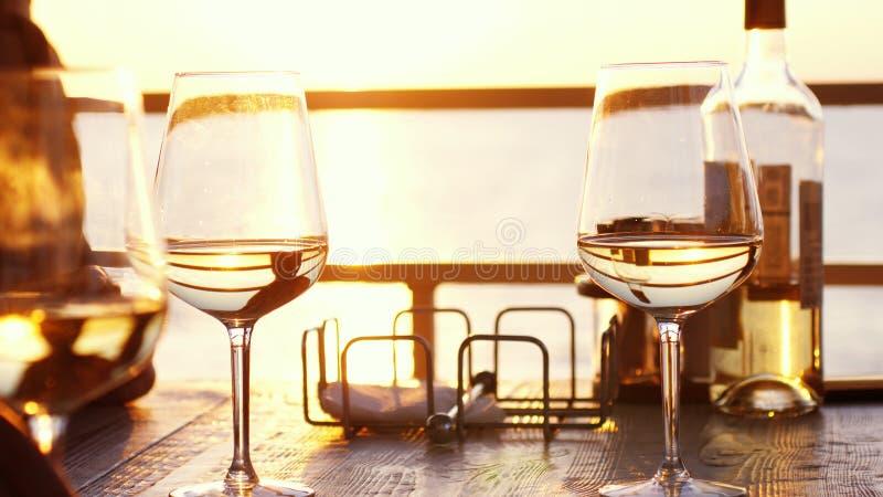 Ένα ρομαντικό γεύμα το καλοκαίρι σε μια παραλία στο ηλιοβασίλεμα με δύο ποτήρια του άσπρου κρασιού και ενός μπουκαλιού του κρασιο στοκ φωτογραφία με δικαίωμα ελεύθερης χρήσης