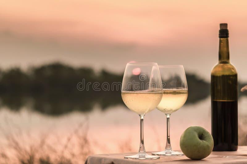 Ένα ρομαντικό γεύμα το καλοκαίρι σε μια παραλία στο ηλιοβασίλεμα με δύο ποτήρια του άσπρου κρασιού στοκ φωτογραφίες