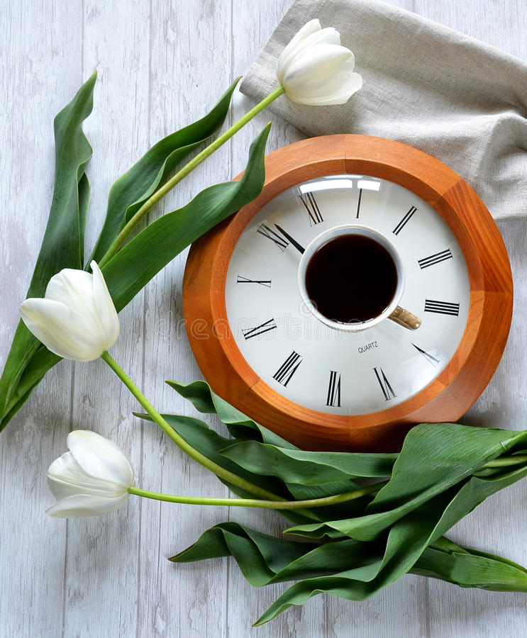 Ένα ρολόι, ένα φλιτζάνι του καφέ και τουλίπες στοκ εικόνα με δικαίωμα ελεύθερης χρήσης