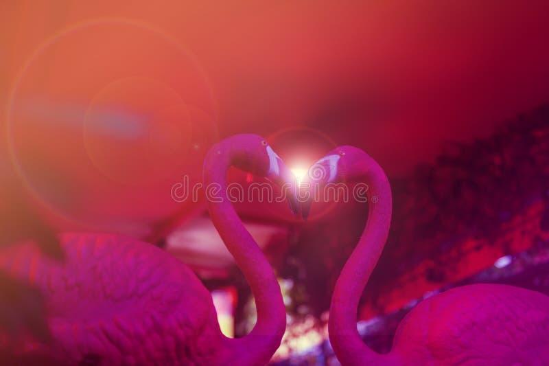 Ένα ρόδινο φλαμίγκο κεραμικό αντιμετωπίζοντας ο ένας τον άλλον για να διαμορφώσει μια μορφή καρδιών στοκ εικόνα