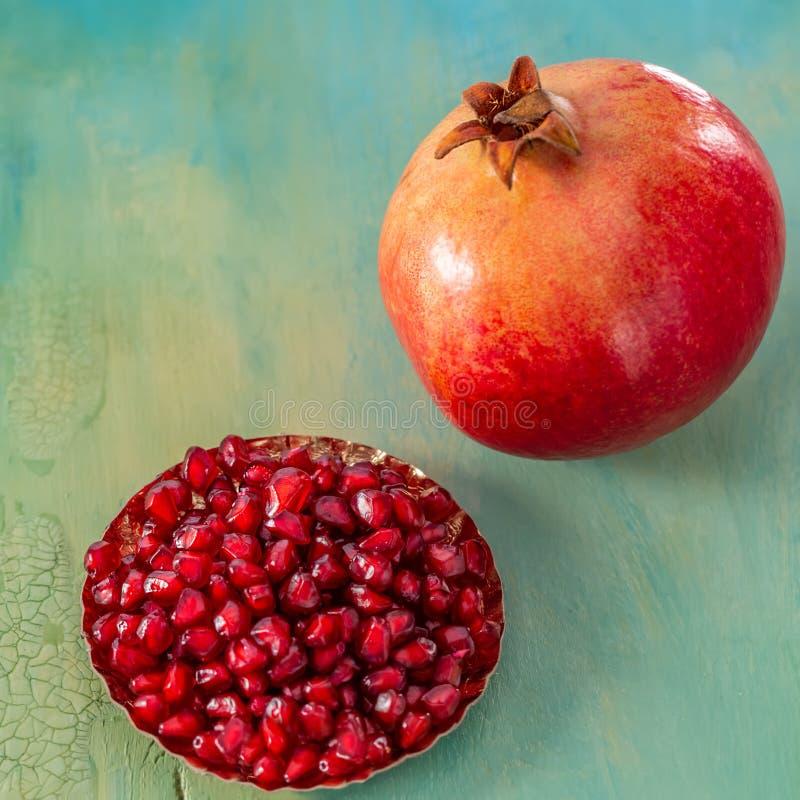 Ένα ρόδι και κόκκινα σιτάρια των φρούτων σε ένα πιάτο στοκ εικόνα