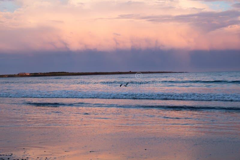 Ένα ρόδινο ηλιοβασίλεμα συμπληρώνει τα σύννεφα θύελλας πέρα από τον ωκεανό στοκ εικόνα με δικαίωμα ελεύθερης χρήσης